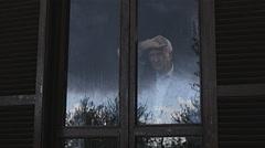 Old depressed man looking the rain behind the window  Stock Footage