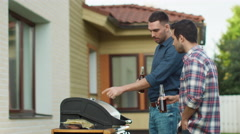 Two Men Preparing Meat on Grill Barbeque Stock Footage