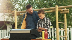 Father and son Cooking Burgers together Stock Footage