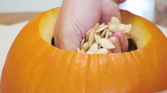 Man Scoops Seeds with His Hands from a Large Orange Pumpkin Stock Footage
