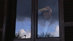 Old retired man at home looking a rainstorm behind the window  Stock Footage