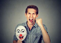 Angry screaming man holding clown mask expressing cheerfulness Stock Photos