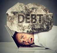 Man squeezed between laptop and rock. Student loan debt concept Stock Photos