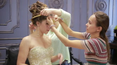Bride preparing to wedding ceremony, help her make-up artist and hairdresser Stock Footage