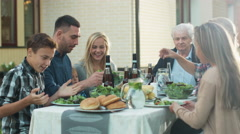 Family gathering around table outdoors Stock Footage