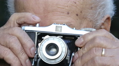 Old man taking pictures with an old film camera: photographing with camera roll  Stock Footage