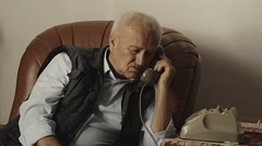 Old man sitting at home dialing disk vintage telephone: rotary phone Stock Footage