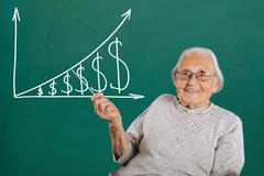 Happy Senior Female Teacher Showing Graph With Pointer On Blackboard Stock Photos