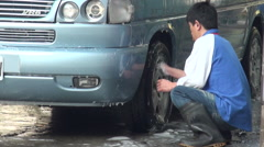 A man is cleaning tires and wheels with a sponge of a van in a car wash. Stock Footage