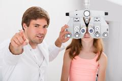 Young Male Optometrist Checking Girl's Vision With Phoropter Stock Photos