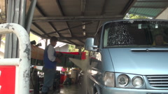 A man is cleaning the side of a van with a water hose pressure in a car wash. Stock Footage
