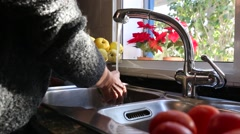 A woman is cleaning a green pepper and vegetables under the tap in the kitchen. Stock Footage