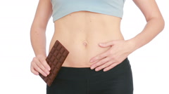 Overweight woman getting dressed wearing jeans and holding chocolate Stock Footage