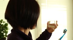 An asian woman is rinsing his mouth with a glass of water. Stock Footage