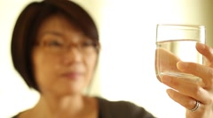 An asian woman with glasses is looking at a glass of water and then drink. Arkistovideo