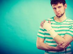 Man with painful bandaged hand. Stock Photos