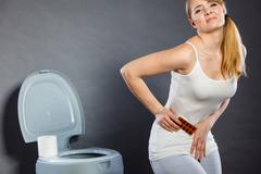 Woman suffer from belly pain holds pills in toilet Stock Photos