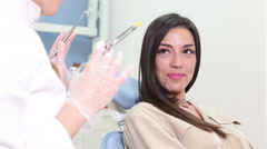 Beautiful female patient faking fear of injection at dentist Stock Footage