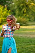Girl holds cup of coffee and a hot dog. Stock Photos