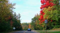Driving into Fall Color on Curving Hilly Road Stock Footage