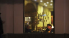 Night cafe through window from street with pedestrians in night city. Stock Footage