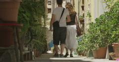 4K Couple walking through narrow street with lots of plants Stock Footage