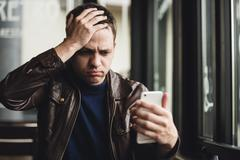 Bad news. Depressed young man expressing negativity while reading message on the Stock Photos