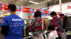 Pan shot of people paying foods at self-check out counter inside Superstore Stock Footage