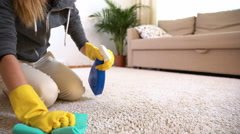 Housewife cleans the carpet with special detergent. Stock Footage