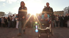 Family with Kid in a Wheelchair Walking Through Crowded Square Stock Footage
