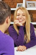 Girl smiling at the guy sitting in a cafe. The first meeting date Kuvituskuvat