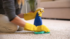 Housewife cleans the carpet with special detergent. Dolly shot. Stock Footage