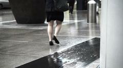 Asian pedestrians walking through rain in business district area on wet floor Stock Footage