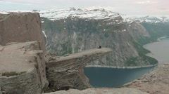 Relaxation on the edge of the Trolltunga. Norway. Smooth dolly shot. Stock Footage