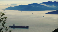 Aerial shot of container cargo ship at beautiful sunset ocean from far Arkistovideo