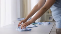 Pregnant woman folding baby boys clothes at home 19 Stock Footage