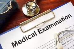 Medical Examination form on a wooden table. Stock Photos