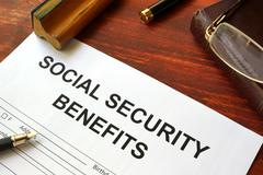 Social security benefits form, book and glasses. Stock Photos