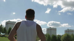 View from the back. Young athletic man in t-shirt  running in the city. Stock Footage