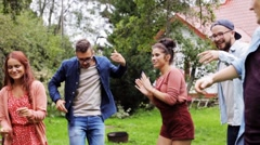 Happy friends dancing at summer party in garden Stock Footage