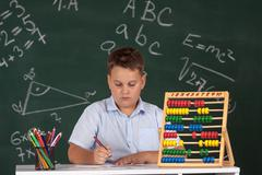 Young boy described at the green blackboard at school thinking about the task Stock Photos
