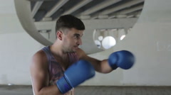 Slow motion. Boxer in a blue boxing gloves is on a training outdoors. Stock Footage
