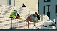 Bricklaying men team work together on white brick house wall Stock Footage