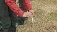Young girls cleans of dirt tent pegs. Norway. Stock Footage