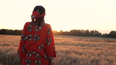African woman in traditional clothes in a field of crops at sunset or sunrise Stock Footage