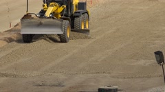 Grader machine leveling gravel rubble on road construction site Stock Footage