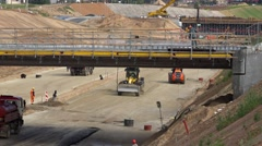 Worker washing concrete viaduct with high pressure tool, earthmover leveling Stock Footage