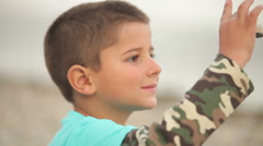 Boy with closed eyes sitting on the beach Stock Footage