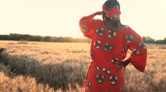 African woman traditional clothes standing in a field of crops at sunset sunrise Stock Footage