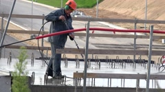 Professional male worker irrigate concrete with water tool on highway viaduct Stock Footage
